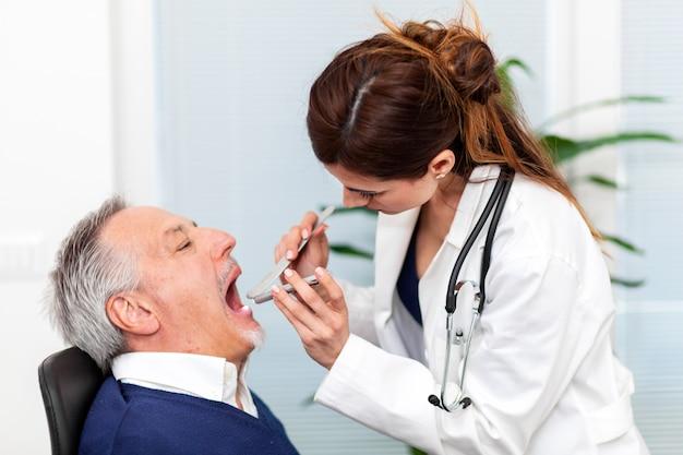 Женщина-врач навещает пациента, проверяя его горло