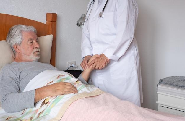 自宅で年配の患者さんを訪ねて体温をチェックする女医。ベッドに横臥を心配している老人