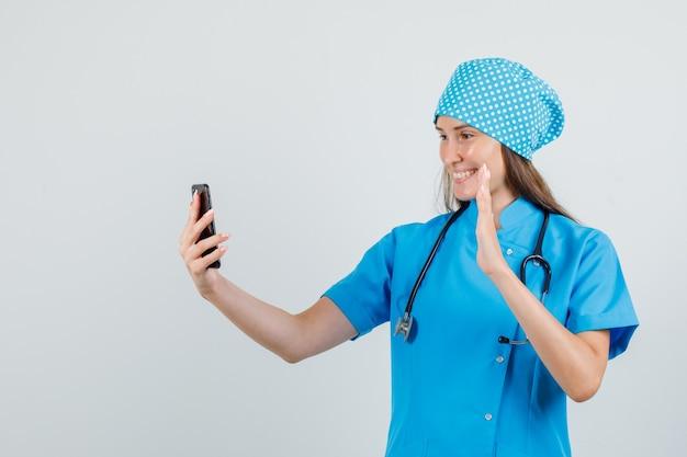 Dottoressa agitando la mano sulla videochiamata in uniforme blu e guardando allegra