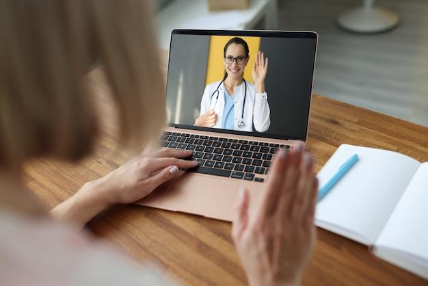 Женщина-врач машет привет далекому пациенту