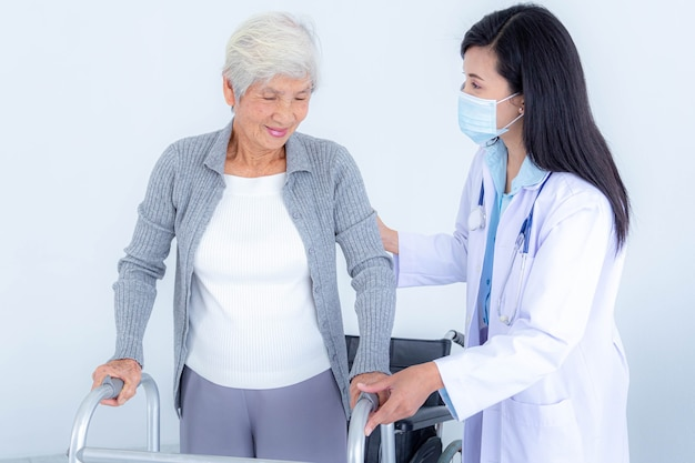 Женщина-врач в медицинской маске, поддерживающая старшую женщину с помощью ходунка. уход за пожилыми пациентами и здравоохранение, медицинская концепция.