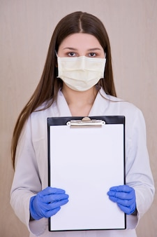 Female doctor wearing protection face mask holding notes.