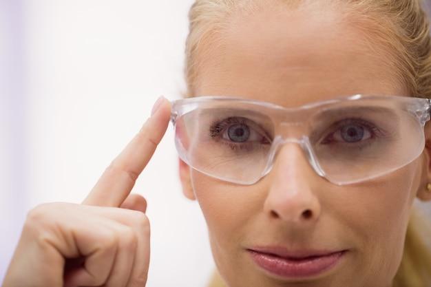 Medico femminile che indossa gli occhiali protettivi in clinica