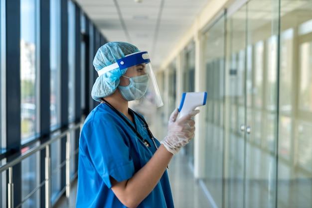 병원에서 체온을 확인하기 위해 적외선 온도계를 사용하여 보호 마스크와 얼굴 방패를 착용하는 여성 의사. 코로나 19