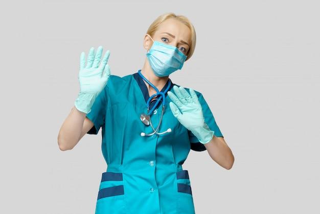 防護マスクとラテックス手袋を身に着けている女性医師が怖がって強調