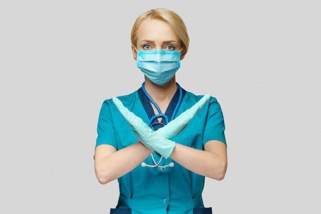 Женский доктор нося защитную маску и латексные перчатки останавливает жест знака