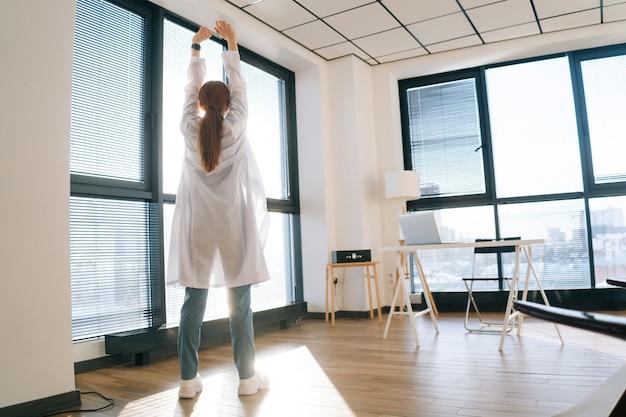晴れた日に窓の背景に手を伸ばす白衣を着た女性医師