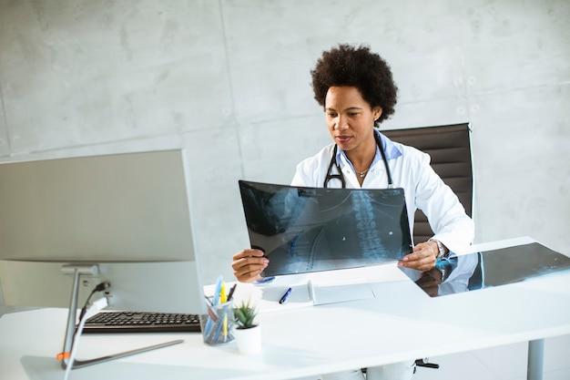 청진기는 사무실에서 책상 뒤에 앉아 엑스레이 이미지를 찾고 흰색 코트를 입고 여성 의사