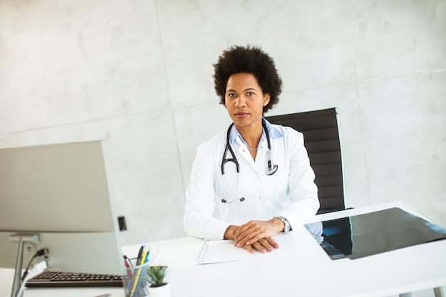 청진기는 사무실에서 책상 뒤에 앉아 흰색 코트를 입고 여성 의사