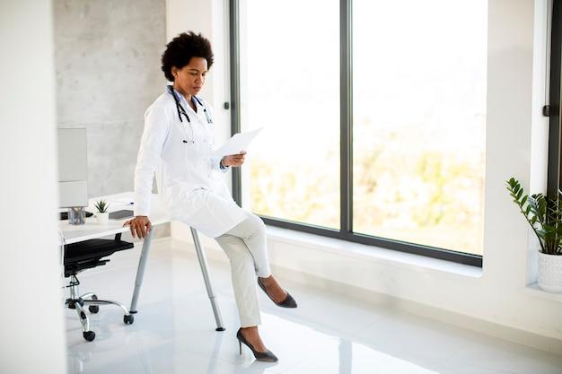 聴診器で白衣を着てオフィスの机のそばに立って、紙の上の医療検査結果を見ている女性医師