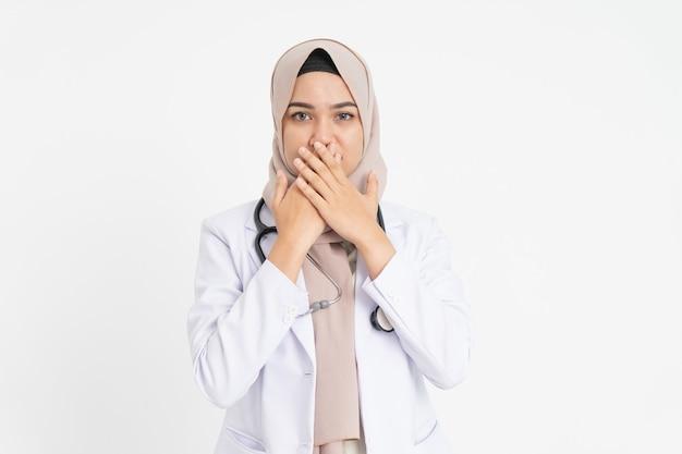 하얀 양복을 입은 여성 의사가 양손으로 입을 가리고 있다