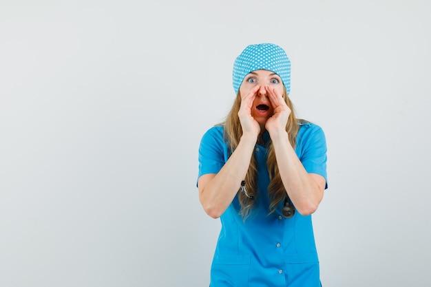 Medico femminile che bisbiglia pettegolezzi in uniforme blu e che sembra sorpreso