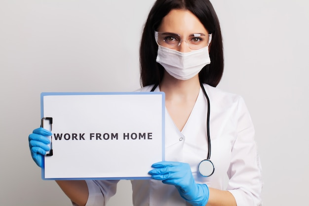 Female doctor in a white coat holding the inscription work from home
