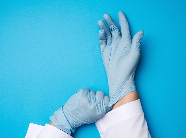 Female doctor in a white coat puts on her hands blue latex sterile medical gloves on her hands