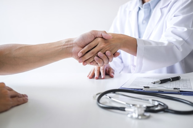 Female doctor in white coat shaking hand with patient after successful recommend treatment methods