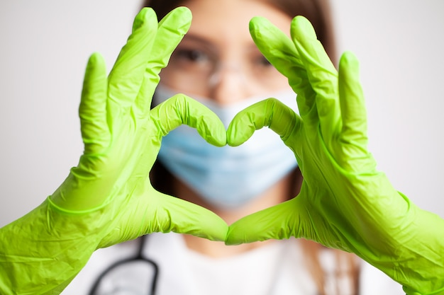 Female doctor in white coat shows hand a heart sign