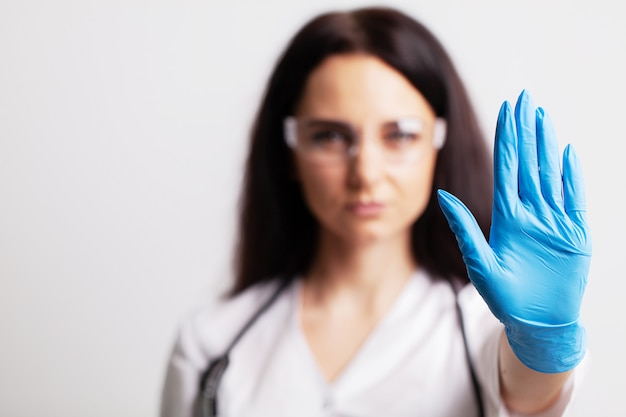 Female doctor in white coat shows hand stop