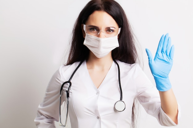 Female doctor in white coat shows hands stop gesture