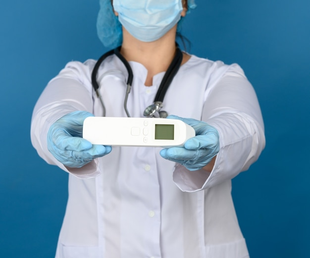 Female doctor in a white medical coat, blue latex gloves holding a plastic electronic non-contact thermometer, blue background