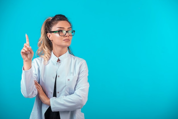 Female doctor in white uniform asking for attention.