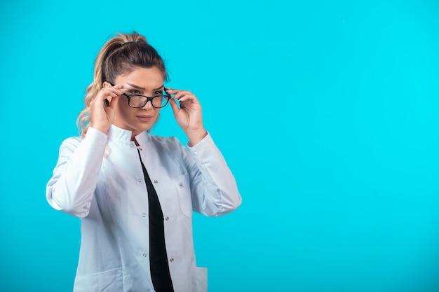 Female doctor in white uniform wearing eyeglasses.