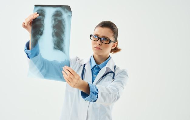 Женщина-врач с рентгеновским снимком на светлом фоне и модель эмоций медицинский халат. фото высокого качества