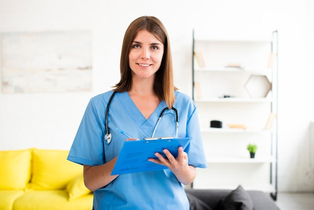 Female doctor with blue clipboard looking at the camera