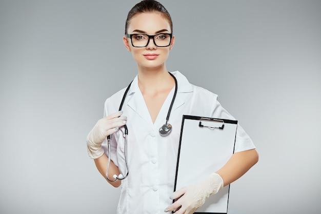 Женщина-врач с каштановыми волосами и обнаженной кожей составляет белую медицинскую форму, очки, стетоскопы и белые перчатки на сером фоне студии и держит заметки.