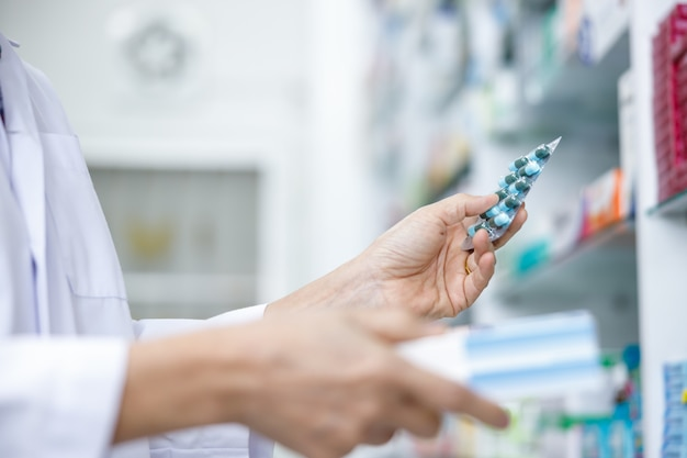 Female doctor with capsule medicine packs on holding hand in pharmacy store thailand