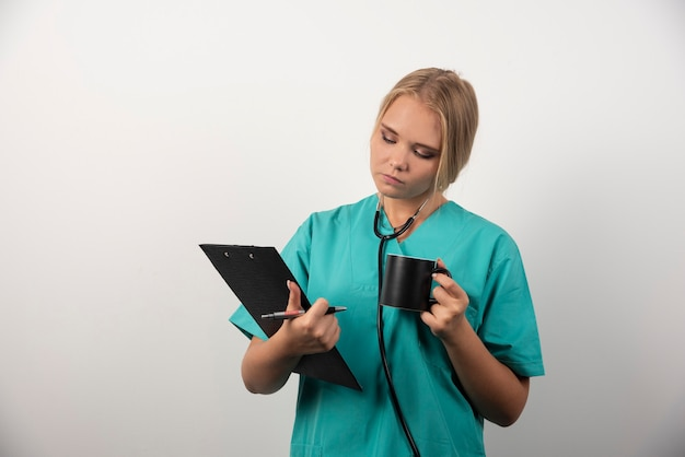 クリップボードを見ているカップを持つ女性医師。