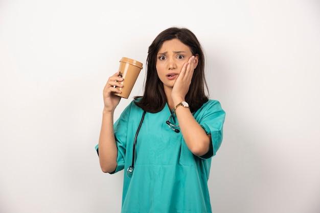 Женщина-врач с чашкой кофе, держа ее за щеку на белом фоне. фото высокого качества