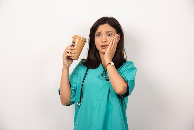 白い背景に彼女の頬を保持しているコーヒーのカップを持つ女性医師。