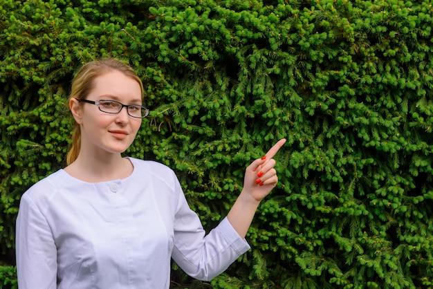 손가락으로 여성 의사 녹색 단풍 배경에 가리 킵니다. 식품 및 의료 산업의 과학적 발전