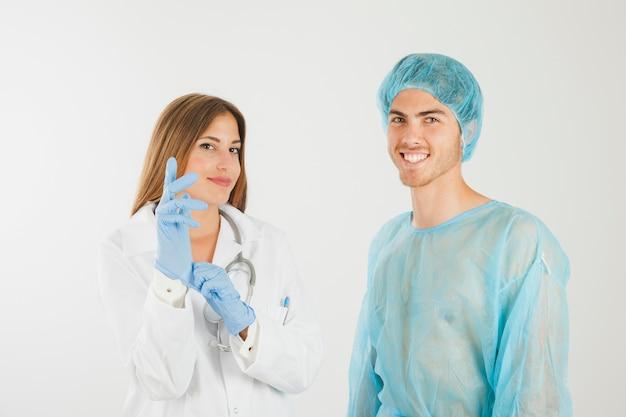笑顔の患者の隣に手袋を持つ女性医師