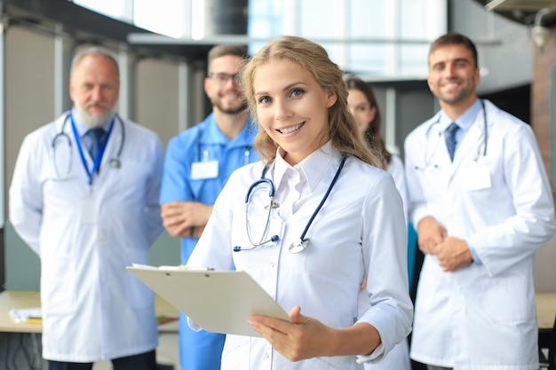 幸せな成功した同僚のグループを持つ女性医師。