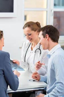 Женщина-врач со своими пациентами в клинике что-то объясняет