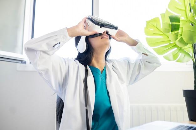 ノートパソコンとバーチャルリアリティメガネをかけた女性医師