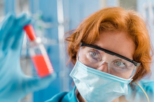 Женский доктор с маской, глядя на образец