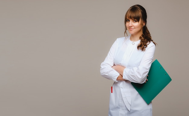 A female doctor with a notebook in her hands on a gray wall