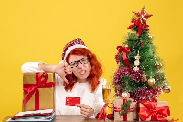 黄色のプレゼントと銀行カードを持つ女性医師
