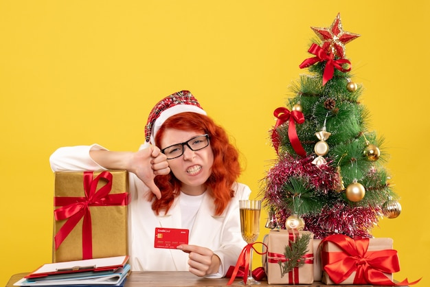Female doctor with present and bank card on yellow