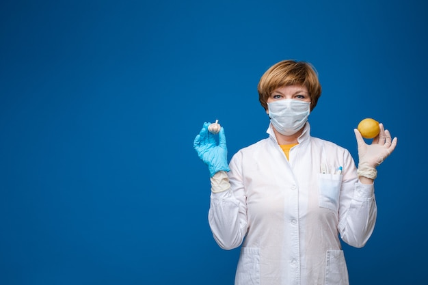 Female doctor with protective glasses and mask holding food