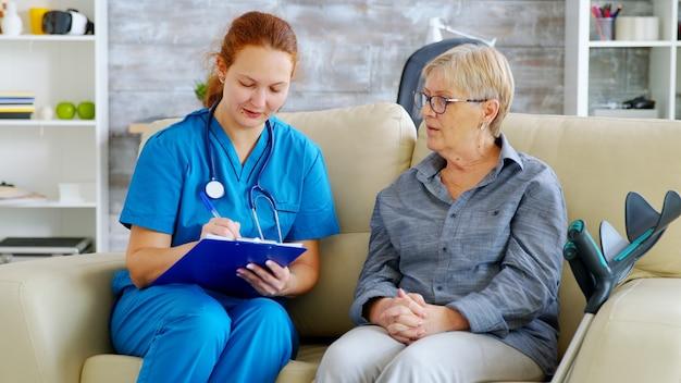 ナーシングホームのソファで年配の女性と話している間クリップボードにメモを取る赤い髪の女医師