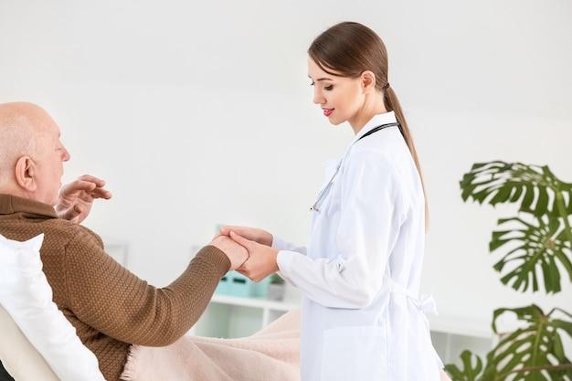 클리닉에서 파킨슨 증후군으로 고통받는 노인과 여성 의사