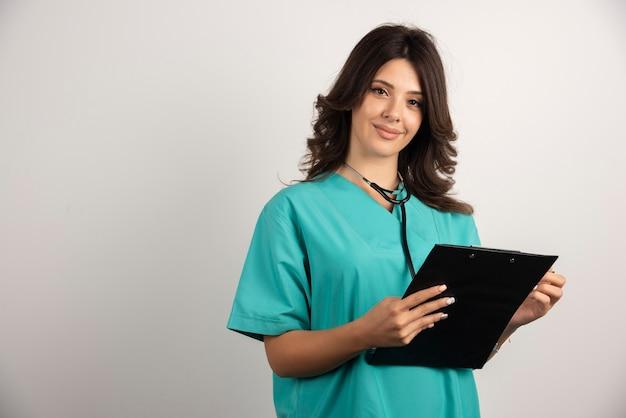 カメラを見ている聴診器とクリップボードを持つ女性医師。