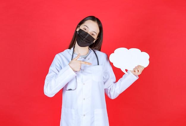 청진 기 및 구름 모양 빈 정보 데스크를 들고 검은 마스크 여성 의사.