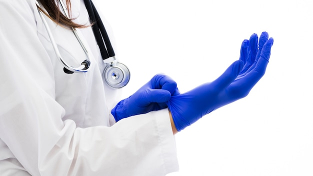 Female doctor with stethoscope around her neck wearing the blue surgical gloves against white backdrop