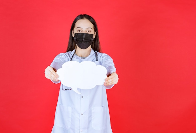 Medico femminile con lo stetoscopio e nella maschera nera che tiene un banco informazioni in bianco a forma di nuvola.