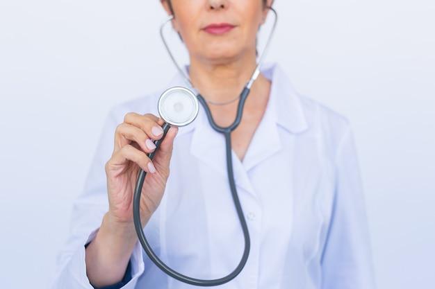 Женщина-врач со стетоскопом, крупным планом над белой стеной