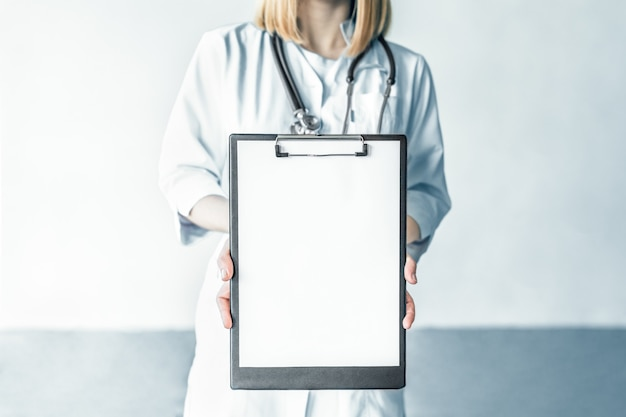 Female doctor with stethoscope holding clipboard on white background